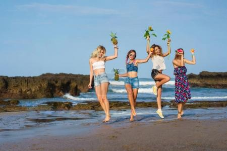 Photo for Group of happy young women with fruits and sunflowers on beach - Royalty Free Image