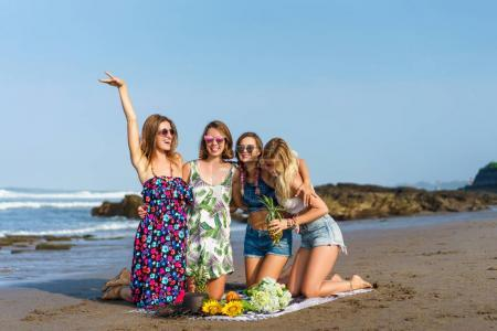 group of happy young women with various fruits spending time on beach