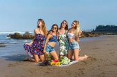 group of attractive young women with various fruits spending time on beach