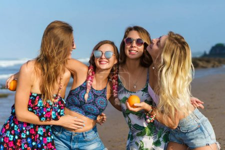 group of happy young women embracing on beach