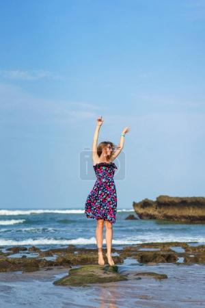 Photo for Happy young woman in dress jumping on beach - Royalty Free Image