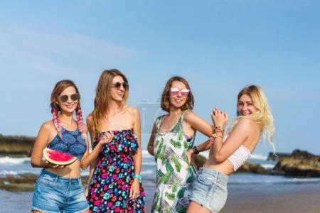group of beautiful young women with slice of watermelon spending time on beach