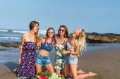 group of beautiful young women with various fruits spending time on beach