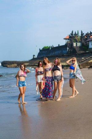group of stylish young women in bikini posing on beach
