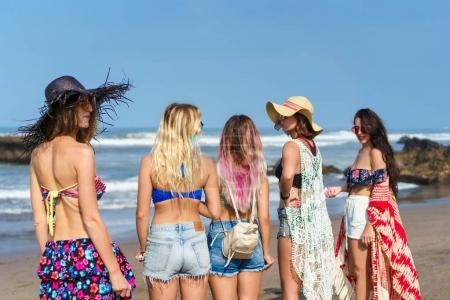 rear view of group of beautiful young women on beach