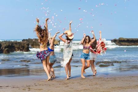 Foto de Grupo de hermosas mujeres jóvenes divirtiéndose y vomitando de pétalos en la playa - Imagen libre de derechos