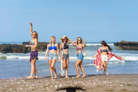 group of beautiful young women spending time together on beach