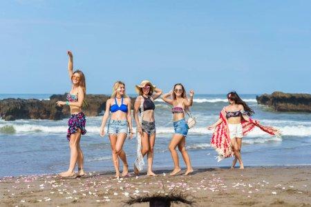 Photo pour Groupe de belles jeunes femmes passant du temps ensemble sur la plage - image libre de droit