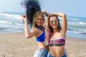 happy young women in bikini on sea coast