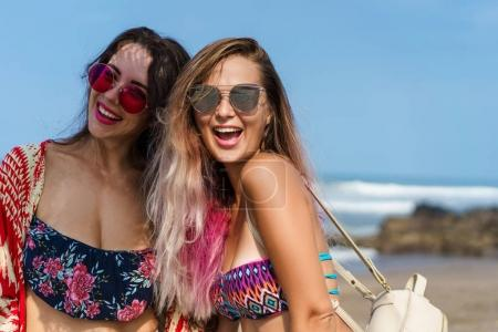 Photo for Happy young women in bikini and sunglasses together on beach - Royalty Free Image