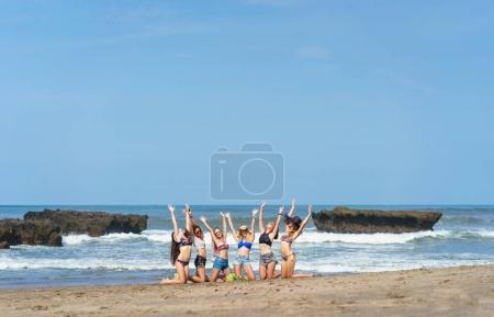 group of celebrating young women with raised hands on beach