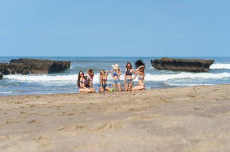 Foto de Grupo de hermosas mujeres jóvenes sentados juntos en la playa - Imagen libre de derechos