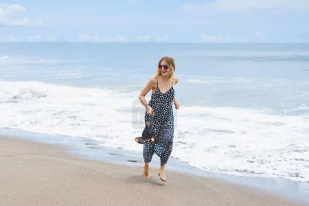 beautiful barefoot girl in long dress running on beach near ocean