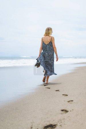 Photo for Rear view of blonde woman in long dress walking on sandy beach near ocean - Royalty Free Image