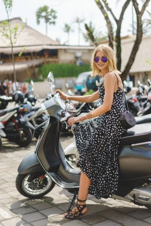 attractive blonde woman sitting on motorbike in city