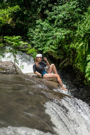 side view of woman in cap resting on rocks near Aling-Aling Waterfall, Bali, Indonesia