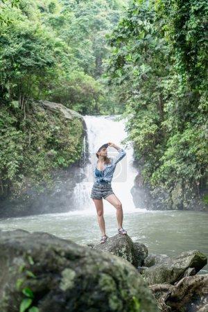 Photo pour Femme debout sur un rocher avec une cascade Aling-Aling et des plantes vertes sur le fond, Bali, Indonésie - image libre de droit