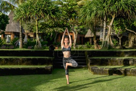attractive woman practicing yoga in tree pose with beautiful green plants on background, Bali, Indonesia
