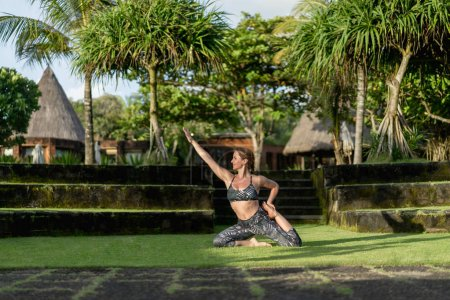 Photo for Woman practicing yoga with beautiful green plants on background, Bali, Indonesia - Royalty Free Image