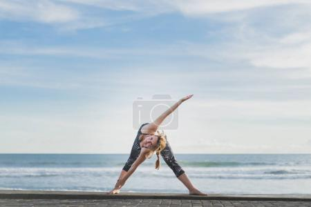 woman in Extended Triangle yoga pose with ocean and blue sky on background, Bali, Indonesia