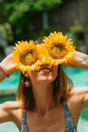Photo for Beautiful smiling girl in bikini holding sunflowers at sunny day - Royalty Free Image