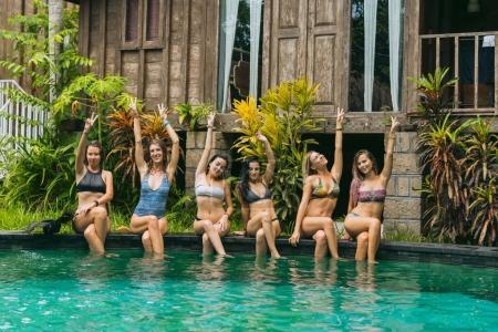 Photo pour Belles jeunes femmes en maillot de bain assis à la piscine et souriant à la caméra - image libre de droit