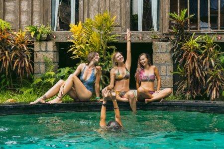 Photo pour Heureux jeunes femmes en maillot de bain s'amuser près de piscine - image libre de droit