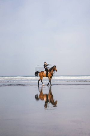 distant view of female equestrian riding horse on beach