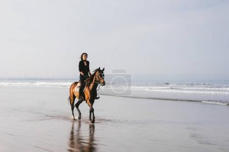 woman riding horse on sandy beach with ocean behind