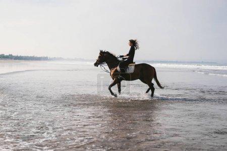 Photo pour Équitation aux jeux femelle jeune cheval dans l'eau - image libre de droit