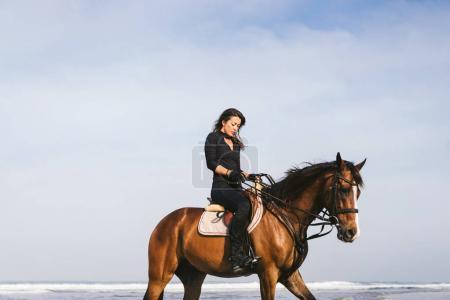 Photo pour Vue d'angle faible de jeunes femelles équestre assis sur le cheval - image libre de droit