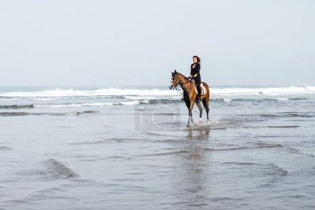 Photo pour Vue distante du cheval de l'équitation équestre féminin dans l'eau - image libre de droit