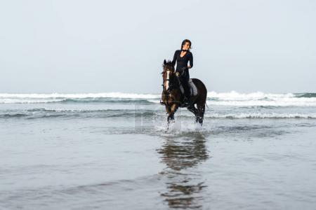 Photo pour Vue de face de jeune femme cheval en eau ondulée - image libre de droit