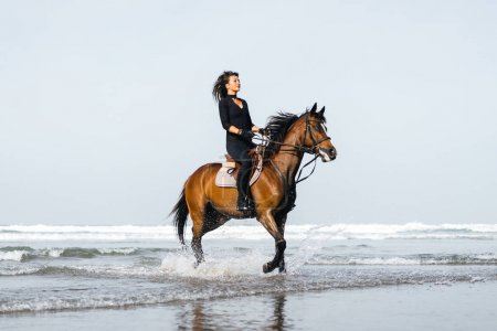 Photo for Young female equestrian riding horse in wavy water on sandy beach - Royalty Free Image