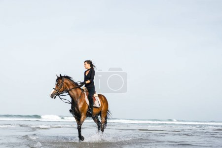 young female equestrian riding horse in wavy water