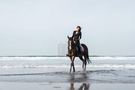 Photo pour Vue de face du cheval de l'équitation équestre féminin dans l'eau ondulée - image libre de droit