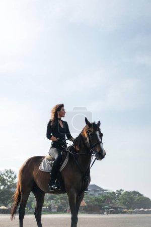 Photo pour Vue faible angle de femelles équestre assis sur le cheval - image libre de droit