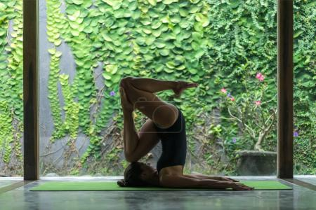 side view of athletic young woman practicing yoga in entrance into Plow pose (Halasana) in front of wall covered with green leaves