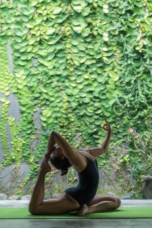 Photo pour Vue latérale du yoga pratique belle jeune femme dans un pattes roi Pigeon poser (Eka Pada Rajakapotasana) sur la terrasse devant le mur recouvert de feuilles vertes - image libre de droit