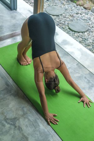 high angle view of beautiful young woman practicing yoga in Downward-Facing Dog pose (Adho Mukha Svanasana)