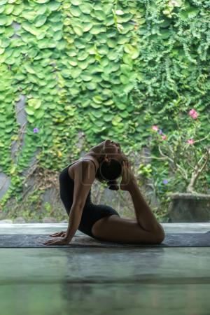 Side view of beautiful young woman practicing yoga and performing back bend with feet  touching head in front of wall covered with green leaves