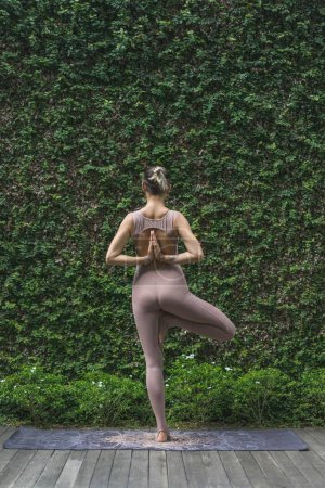 Photo for Rear view of young woman practicing yoga in Tree pose (Vrksasana) in front of wall covered with green leaves - Royalty Free Image
