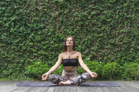 meditating young woman practicing yoga in lotus pose in front of wall covered with green leaves