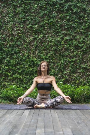 Photo for Calm young woman practicing yoga in lotus pose in front of wall covered with green leaves - Royalty Free Image