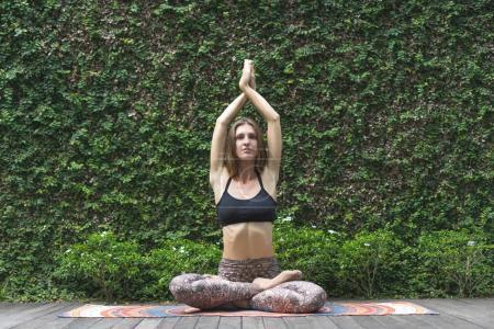 fit young woman practicing yoga in lotus pose with raised hands making namaste gesture in front of wall covered with green leaves