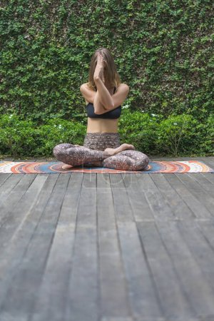 young woman practicing yoga in lotus pose in front of wall covered with green leaves