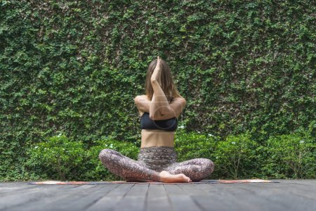 attractive young woman practicing yoga in lotus pose in front of wall covered with green leaves