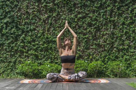 Photo pour Belle jeune femme pratiquant le yoga en pose de lotus avec mudra namaste élevé devant le mur recouvert de feuilles vertes - image libre de droit