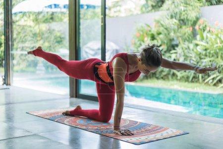 Photo pour Jeune femme sportive pratiquant le yoga en équilibre pose de chat (Utthita Cakravakasana ) - image libre de droit