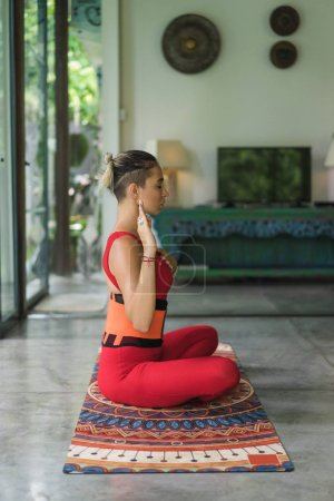 side view of beautiful young woman practicing yoga in lotus pose with hand on heart at home